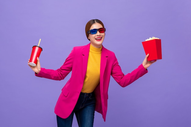 Woman wearing 3d glasses watching movie with drink and popcorn