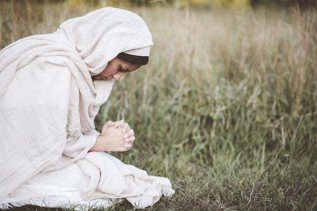 祈りながら聖書のローブを着て膝を下にした女性