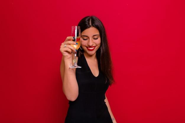 黒のドレスを着て、赤でポーズをとってシャンパングラスを保持している女性
