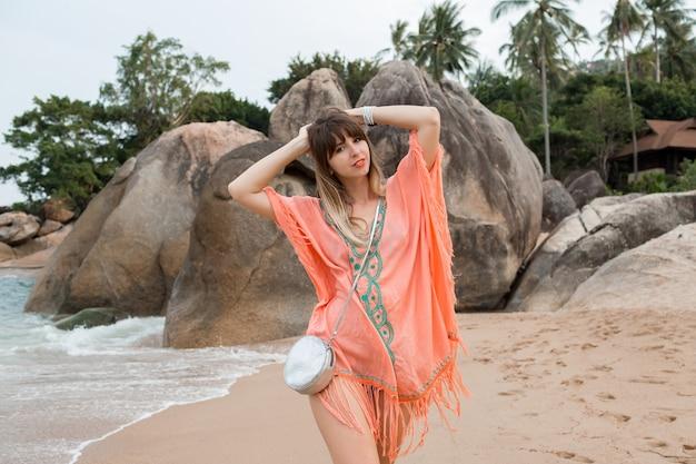 Женщина в платье в стиле бохо гуляет по пляжу со скалами и пальмами