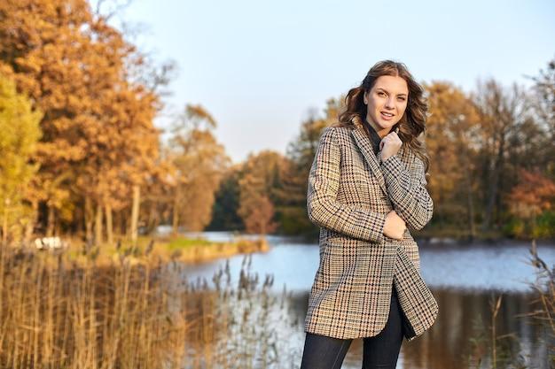 コートを着て、公園に立っている女性