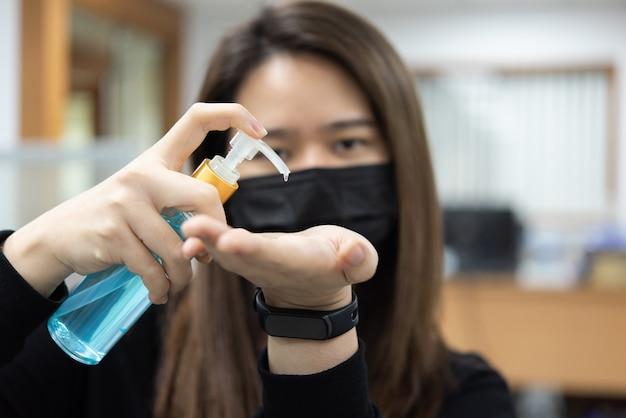 Женщина носит маску и использует дезинфицирующее средство