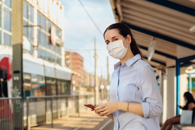 フェイスマスクを着用し、電話をかけ、路面電車が駅に到着するのを待つ女性。新しい通常のコンセプト