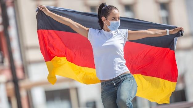 마스크를 쓴 여성이 뒤에 독일 국기를 들고 있다.