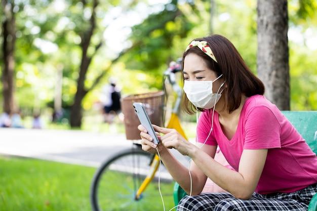 緑豊かな公園のベンチで屋外で音楽を聴くためにスマートフォンを使用して座っているフェイスマスクを身に着けている女性