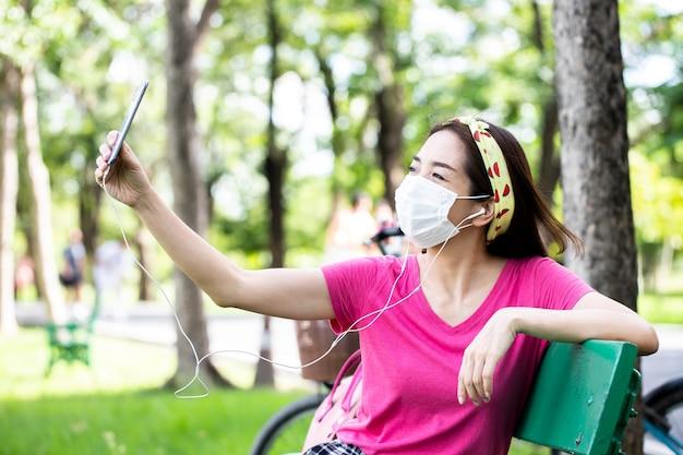 緑豊かな公園のベンチで屋外で写真を撮るためにスマートフォンを使用して座っているフェイスマスクを身に着けている女性