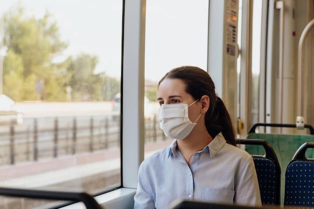 Женщина в маске, путешествующей на трамвае. она смотрит в окно. новая нормальная концепция