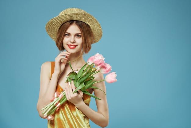 Женщина в шляпе с букетом цветов в подарок на женский день