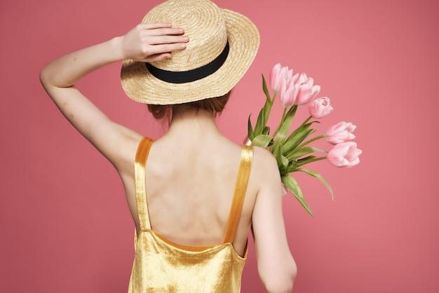 花の後ろのビューの装飾ピンクの背景の帽子の花束を身に着けている女性。高品質の写真