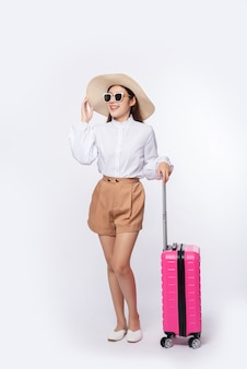 Женщина в шляпе, очках и ручках чемоданов для путешествий