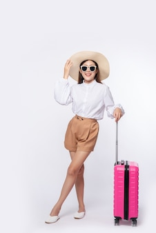 旅行に帽子、眼鏡、スーツケースのハンドルを身に着けている女性