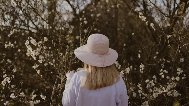 白い花と木の近くに帽子をかぶっている女性
