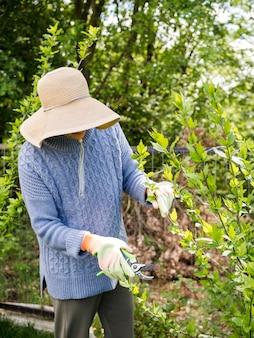 彼女の庭から葉を切りながら帽子をかぶっている女性