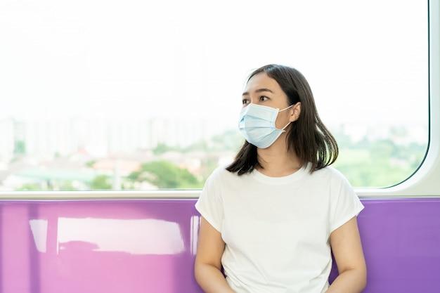 混雑した場所を旅行中にcovid19ウイルスとpm2.5汚染を保護するために衛生保護マスクを着用している女性。女性はフェイスマスクを使用してアジアの国でコロナウイルスの危機を保護します。病気
