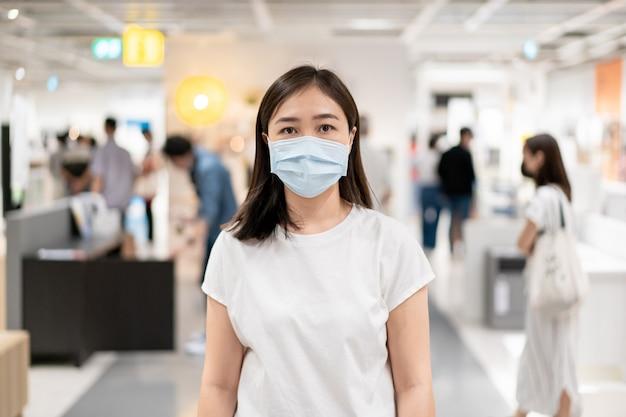 混雑した場所を旅行中にcovid19ウイルスとpm2.5汚染を保護するために衛生保護マスクを着用している女性。
