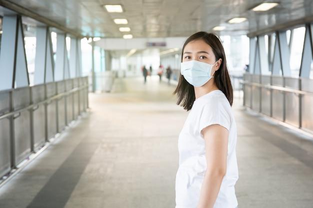 混雑した場所を旅行中にcovid19ウイルス、covid-19およびpm2.5を保護するために衛生保護マスクを着用している女性。女性は、コロナウイルス病を防ぐためにフェイスマスクを使用しています。 2019-ncov危機。