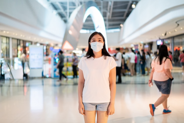 混雑した場所を旅行中にcovid19ウイルス、covid-19およびpm2.5を保護するために衛生保護マスクを着用している女性。女性は、コロナウイルス病を防ぐためにフェイスマスクを使用しています。