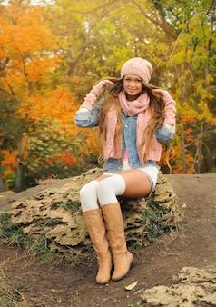 공원에서 니트 모자와 스카프를 착용하는 여자.