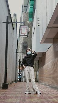 Женщина в маске идет по старому переулку