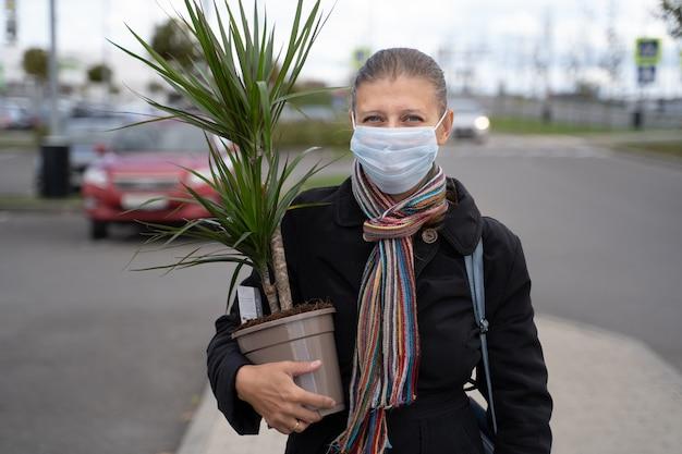 ショッピングモールの駐車場で、covidウイルスから身を守るために顔にマスクをかぶった女性