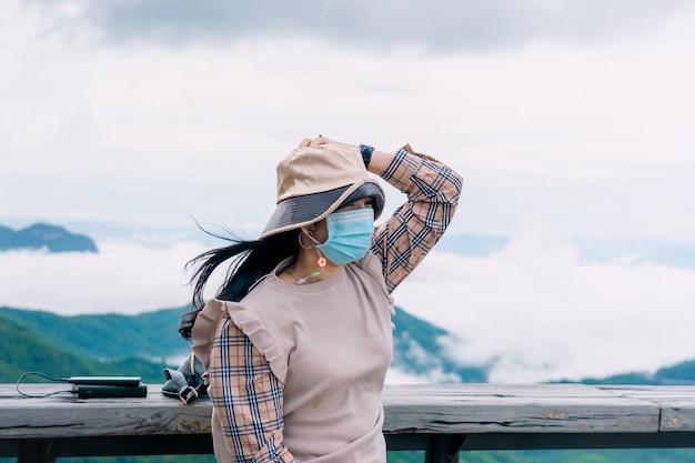 山と霧の景色の旅を見ている木製のバルコニーに座っているマスクを身に着けている女性