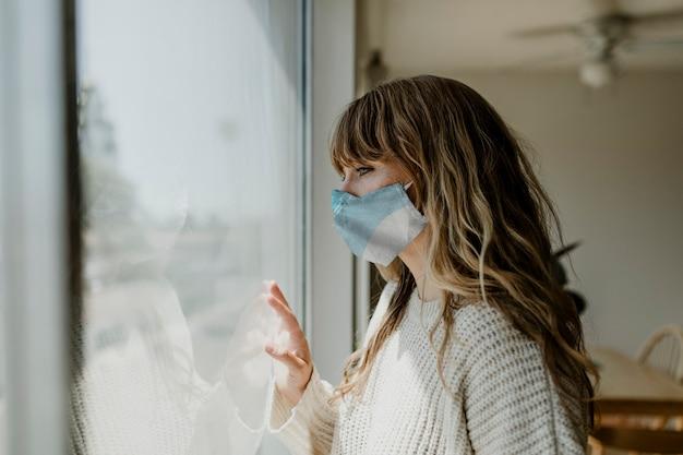 Женщина в маске смотрит в окно во время изоляции