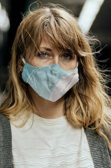 코로나바이러스 전염병 동안 기차를 기다리는 동안 마스크를 쓴 여성