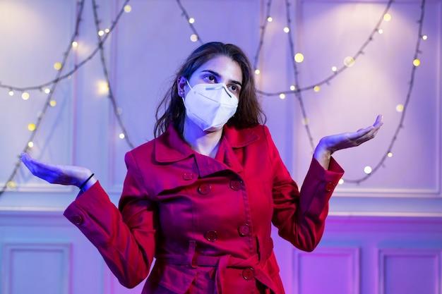 医療用マスクkn95とサンタクロースの赤い帽子をかぶった女性が白いヴィンテージの背景にcovid19の間に自宅で一人でクリスマスを祝う欲求不満の表情
