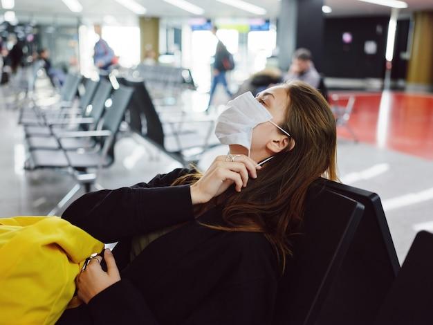 医療用マスクを着用した女性が空港に座って頭を後ろに傾けて待っていた