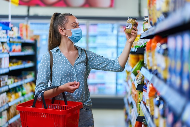 買い物かごで医療用防護マスクを身に着けている女性は食料品店の棚から食品を受け取ります