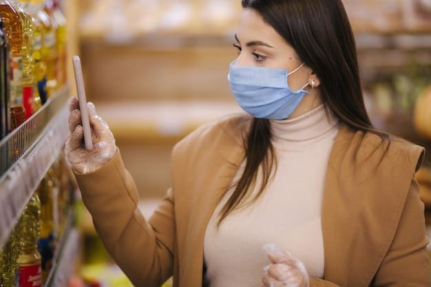 スーパーマーケットで保護マスクと手袋を着用している女性。パンデミック検疫中の買い物
