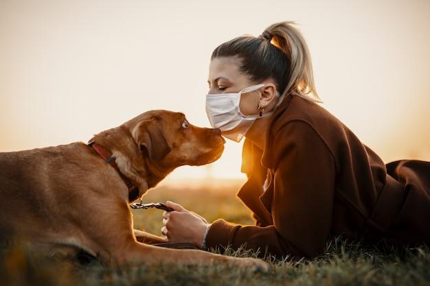 コロナウイルスのパンデミックcovid19のため、保護マスクを着用した女性が犬と一緒に屋外を歩いています