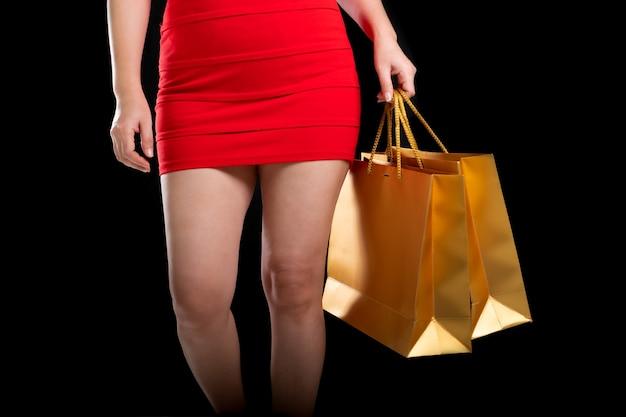 黒い背景の買い物袋を保持している赤いドレスを着ている女性