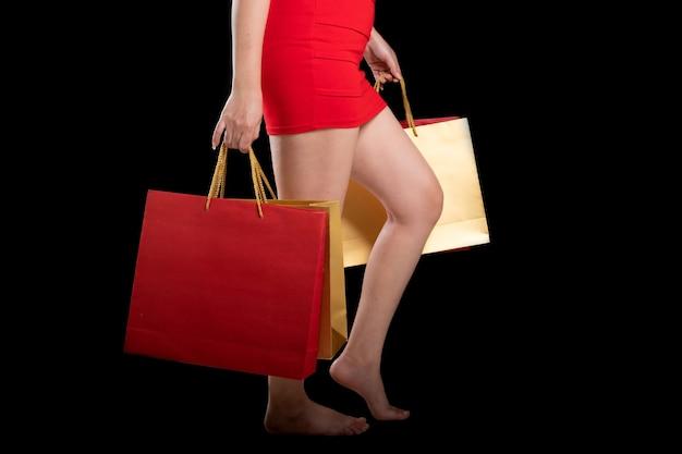 ショッピングバッグを保持している赤いドレスを着ている女性