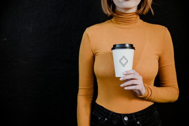 테이크아웃 종이컵 모형이 있는 터틀넥을 입은 여성