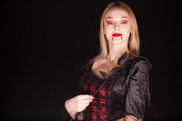검정 배경 위에 장미와 뱀파이어 의상을 입고 여자.