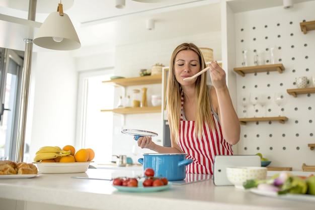 빨간 선이있는 흰색 앞치마를 입고 부엌에서 요리하는 여자