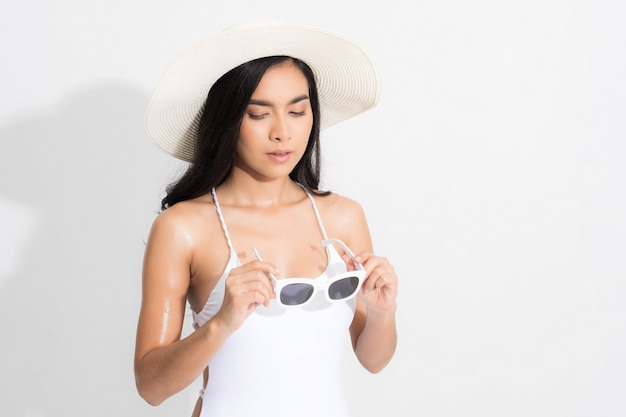 Женщина в белом платье бикини стоя, держа белую белую шляпу и солнцезащитные очки на изолированном белом.