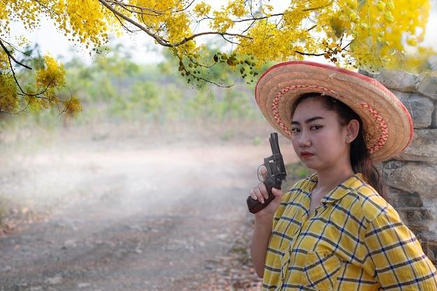 농장에서 오래 된 리볼버 총을 들고 노란색 셔츠 손을 입고 여자와 어린 소녀