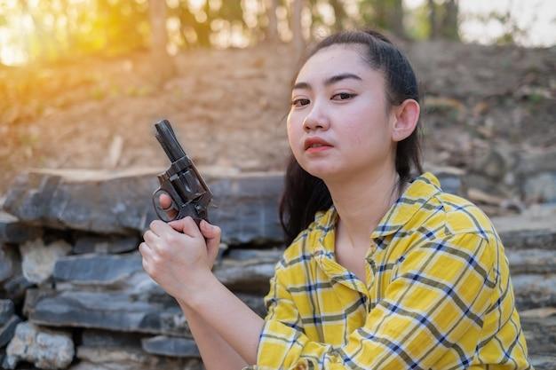 농장에서 오래 된 리볼버 총을 들고 노란색 셔츠 손을 입고 여자