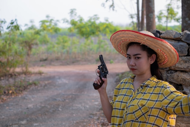 노란색 셔츠를 입고 여자 손을 잡고 오래된 리볼버 총을 농장에서 권총을 든 어린 소녀
