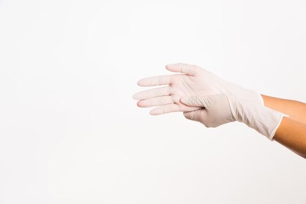 Женщина носит белые резиновые латексные хирургические медицинские перчатки и кладет руку на них