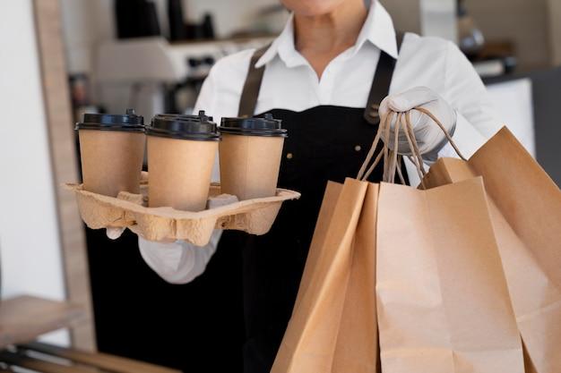 エプロンを着て、持ち帰り用の食べ物とコーヒーカップが入った紙袋を持っている女性 Premium写真