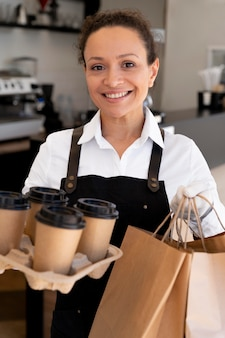Woman wearing apron and holding paper bags with takeaway food and coffee cups