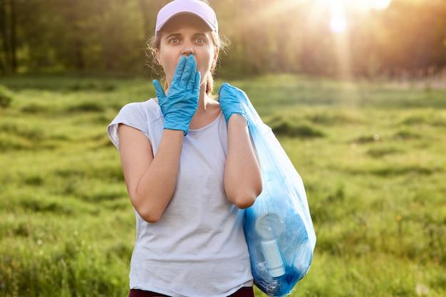 野球帽とカジュアルなtシャツを着て、ゴミ袋を持って、手のひらで口を覆っている女性は、青いラテックス手袋を着用し、ショックを受け、草原でゴミを拾っています。