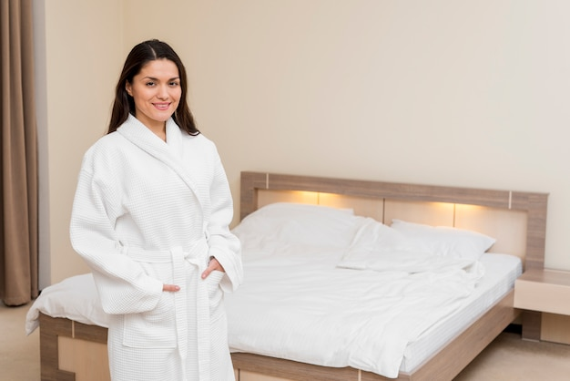 Woman wearing bathrobe in hotel room