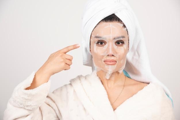 Donna che indossa accappatoio e asciugamano con maschera facciale