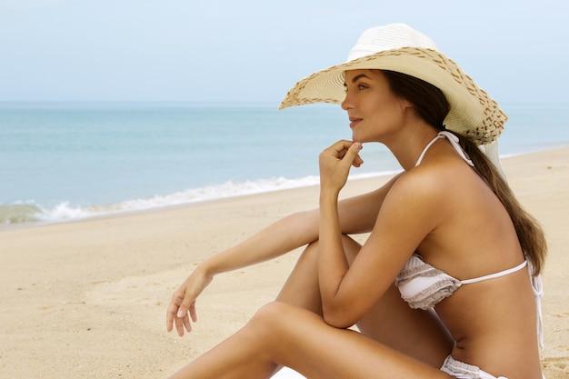 Woman wearing beach hat is sitting beside a sea