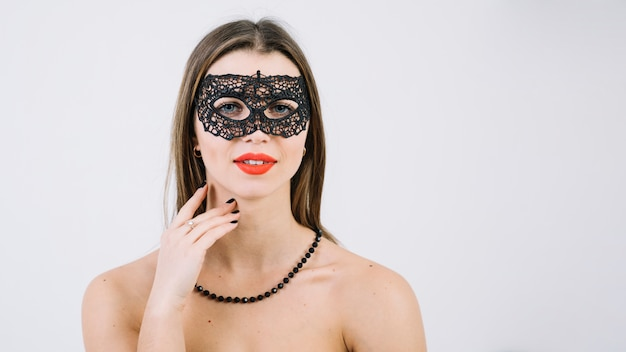 Woman wearing beads necklace in masquerade carnival mask looking at camera