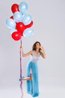 Женщина в красивом платье с большим количеством разноцветных шаров